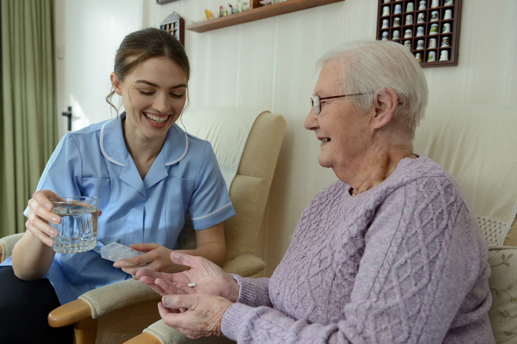 Carer giving medication to elderly lady